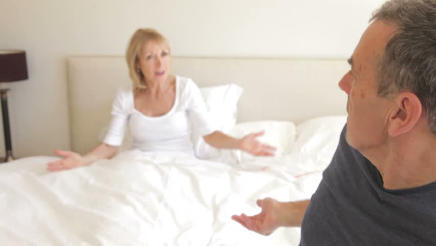 Husband sits on the end of bed arguing with wife who is still in bed.