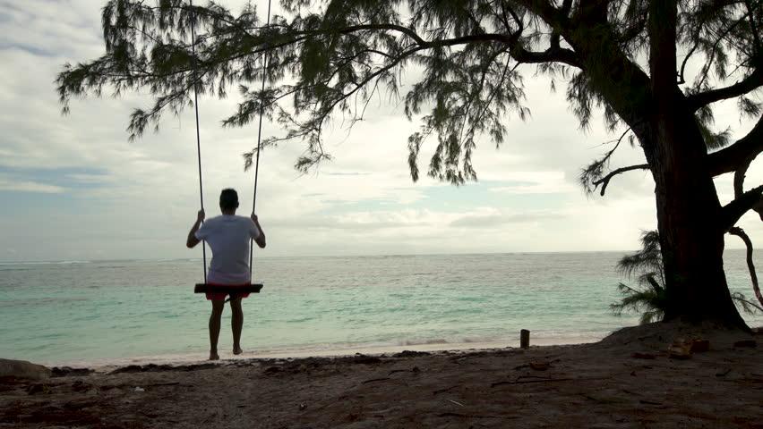 Man on a swing on tropical island beach Punta Cana, Dominican Republic