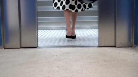 Woman in a skirt get out of an elevator. Close-up of legs