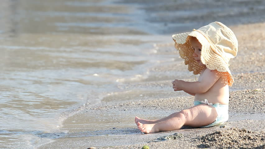 Cute little baby with a big hat sitting on the beach and enjoying the waves
