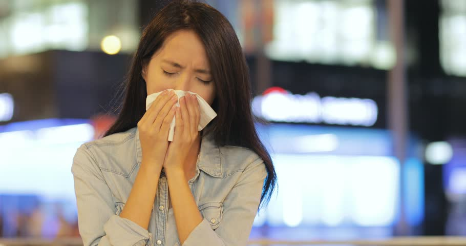 Woman feeling unwell and sneezing at outdoor