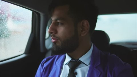 Young muslim businessman riding in the car on passenger's seat. Rain outside the car. Passenger in taxi