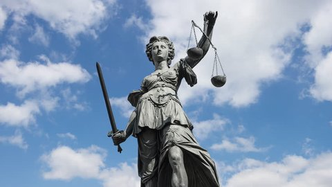 lady justice goddess of Justice zooming in in front of moving clouds, 4k