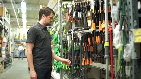 Male customer in garden store choosing manual auger for hole drill for his garden. He taking it from the shelf and looking carefully.