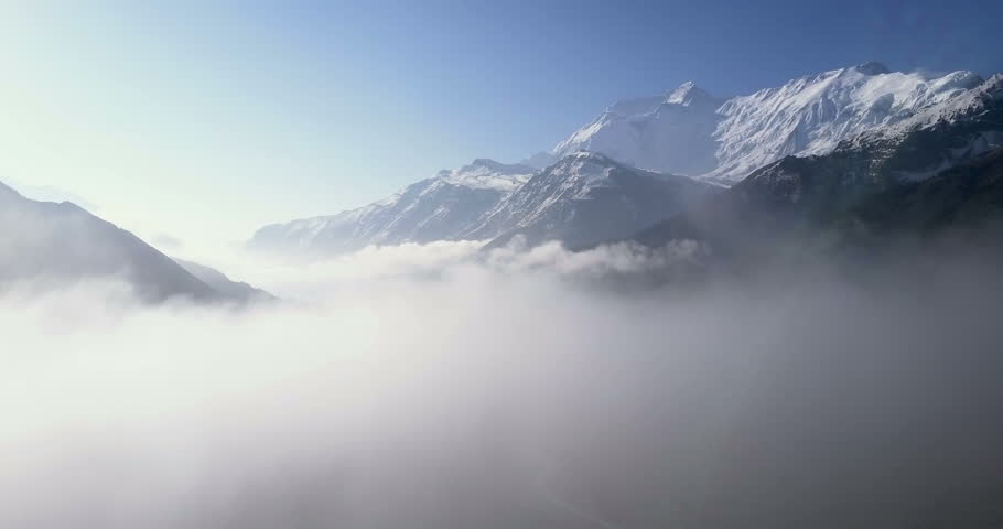 Aerial drone elevating pan above low clouds to reveal snow covered Himalayan Annapurna mountain range in early morning at high altitude above Manang valley landscape in Nepal. 4k 1.9:1 23.976fps