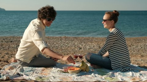 Young couple eating fruit sitting on beach on summer day. Man carefully feeds woman with juicy strawberries, takes big berry and puts it in her mouth.