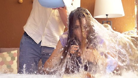 Man making joke to girlfriend splashing bucket of cold water on head slow motion closeup