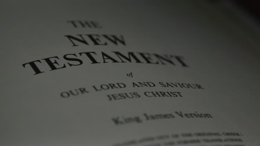 The Bible-  A slow, shallow depth of field, candle lit pan across a page of the Bible that  reveals the heading for the New Testament.