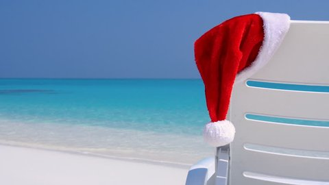 Santa Claus Hat on sunbed near tropical calm beach with turquoise sea water and white sand. Christmas vacation on maldivian island