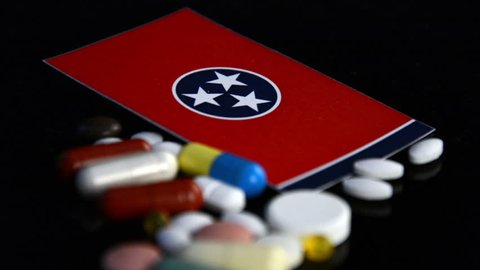 Tennessee State flag with lot of medical pills isolated on black background