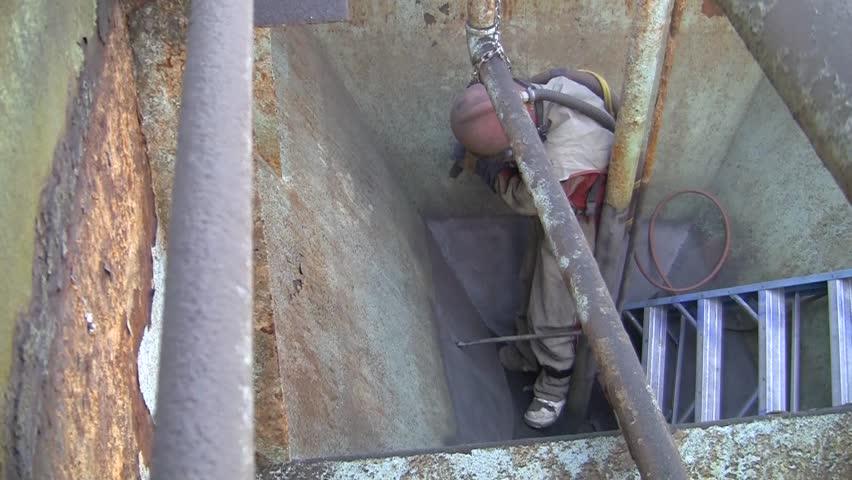 Sandblasting rusted steel tank