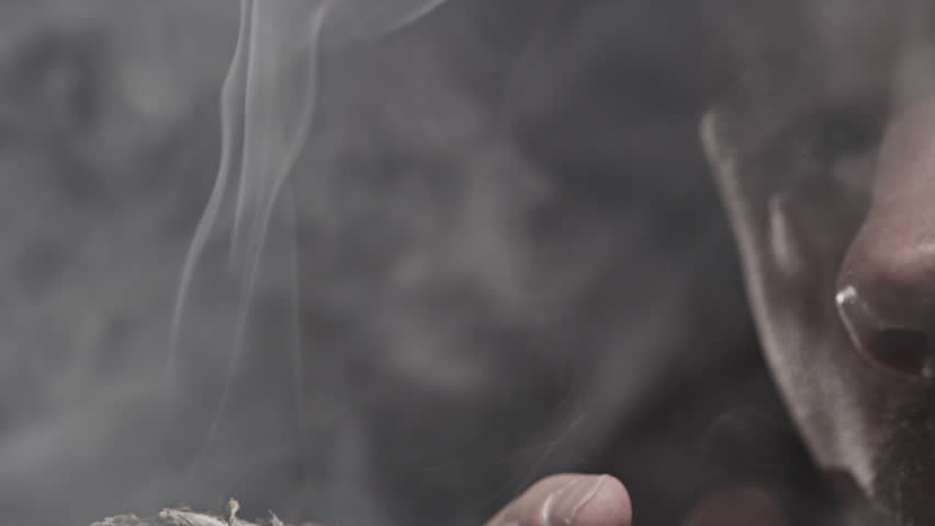 A Man Smokes a Cigar. Takes a big drag and puffs smoke.