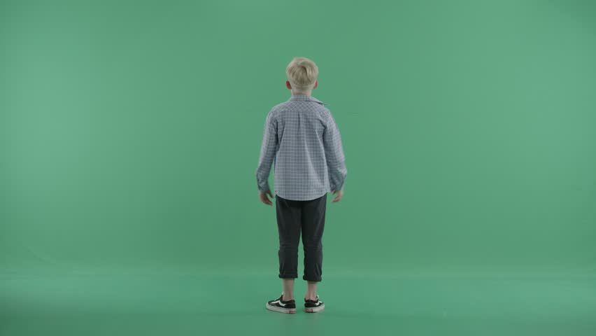 Boy stands back to the viewer jumping and waving hands