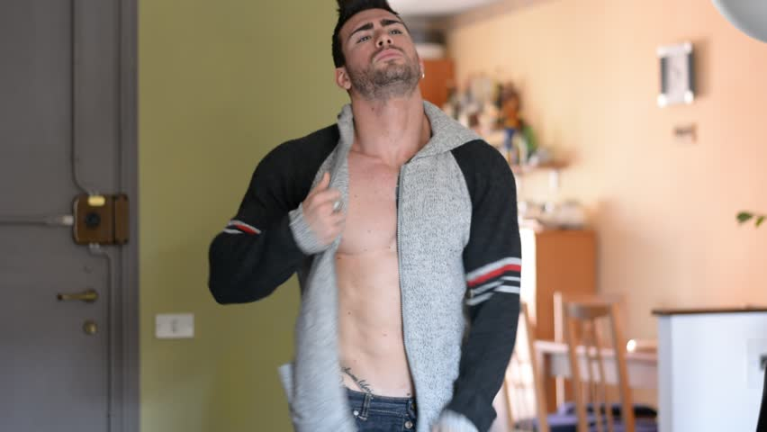 Athletic bodybuilder man opening sweater on naked muscular pecs, abs and torso, undressing and taking it off