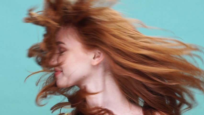Close up of a young pretty girl with long red hair shaking her head isolated over blue background