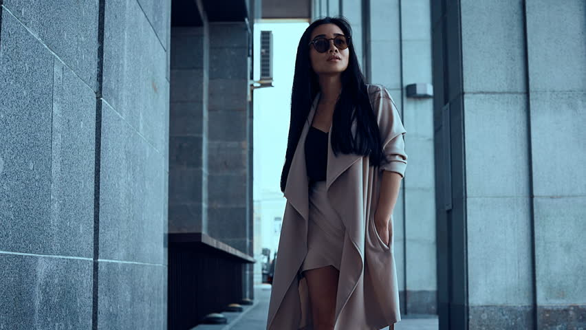Portrait of a cute and gorgeous asian woman in fashion coat walking among the pillars of an old building