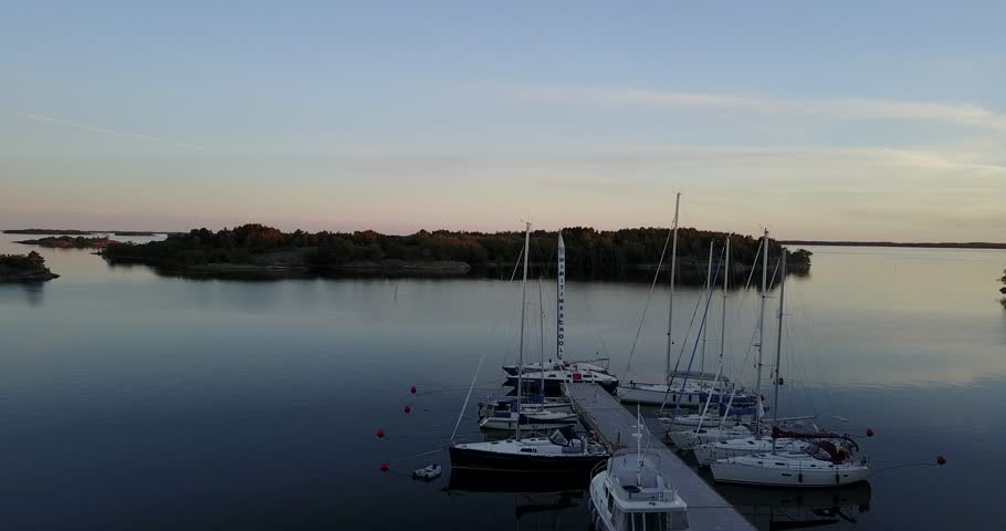 Aerial view: Yachts and boats in the small harbor on Aland (land) Islands at summer sunset. Baltic Sea, Finland - 4K stock footage clip