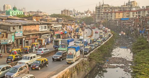 Time lapse shot of vehicles passing on a busy road through slums, while polluted nullah (canal) flowing alongside, Dharavi, Mumbai, India