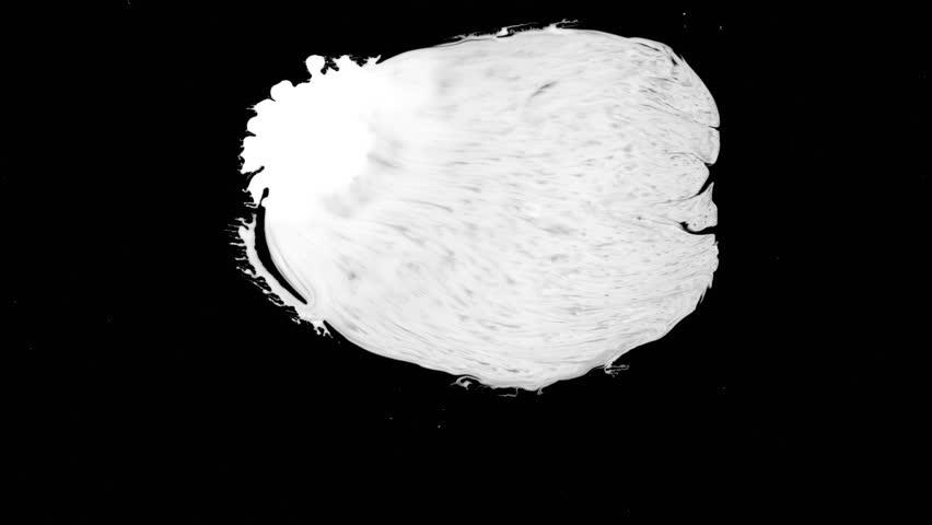 A drop of white liquid splattered over wet black screen background. Close-up shot