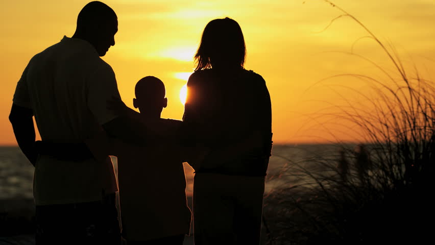 silhouette of happy african american family enjoying sunrise and togetherness on beach holiday red epic