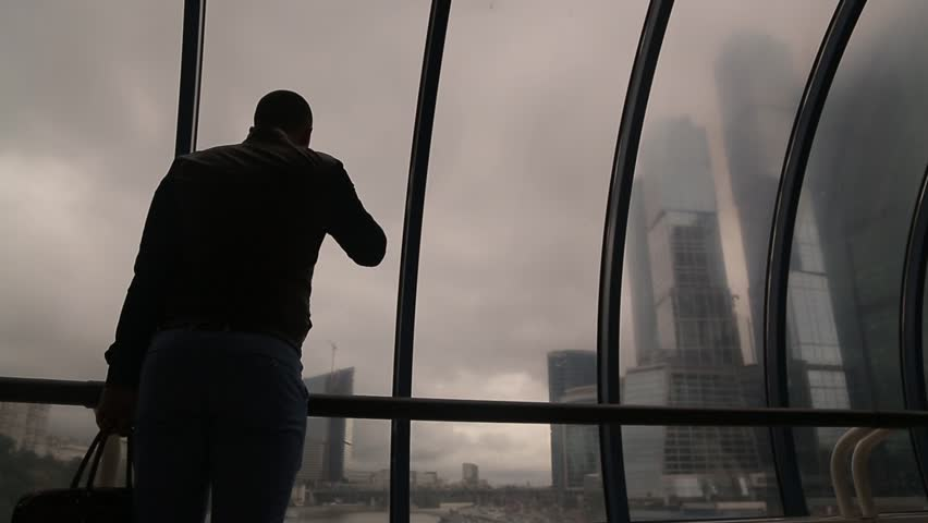 Man with briefcase drinks coffee looking at Moscow City towers at bridge static camera medium shot   Shutterstock HD Video #28981744