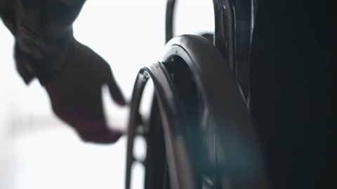 Tracking with close up of silhouette of male hand turning wheels of wheelchair