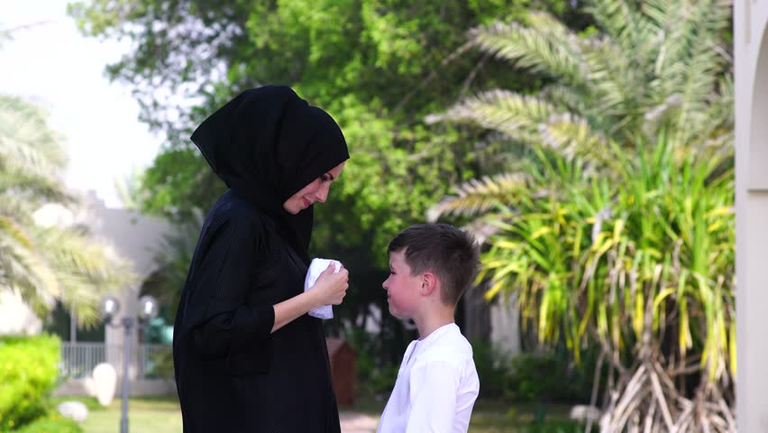 Arabic mother and son play together outdoors.