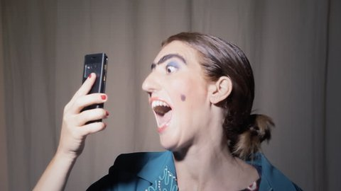 A funny ugly woman (an actor in character) making a series of selfies with a smartphone. Grotesque comedy scene.