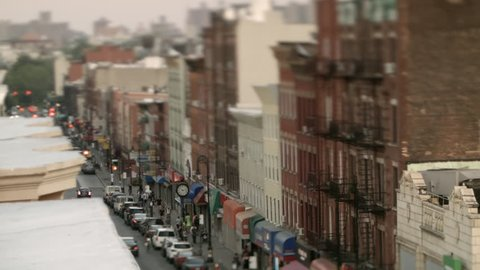 Tilt-shift, magic hour, rooftop view of Manhattan Ave, street in Greenpoint, Brooklyn, New York. Apartment buildings. Fire steps. Storefronts. Cars. Traffic lights. People walking. Focus shifting.