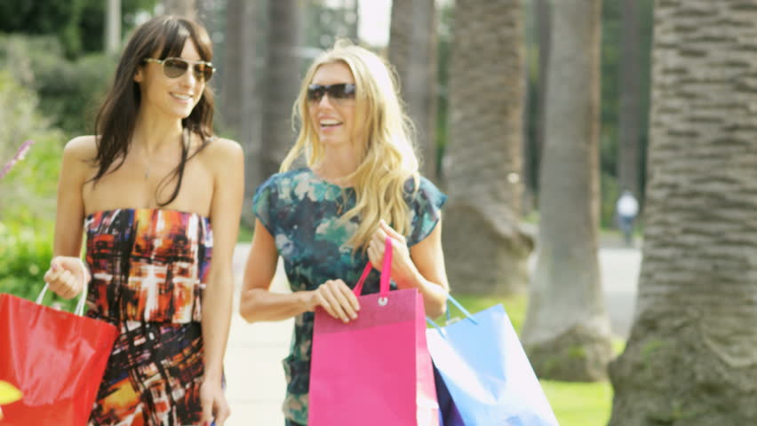 Beautiful tanned young European female friends returning with bags of designer fashion after successful shopping trip RED EPIC | Shutterstock HD Video #29014564