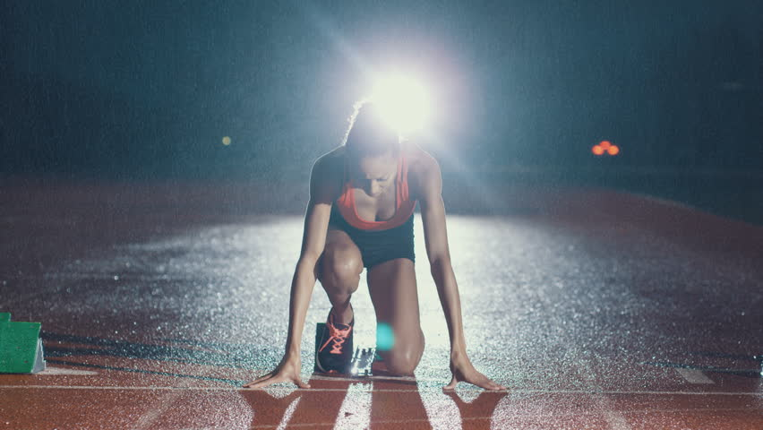 Female athlete training at running track in the dark & in the rain. Slow motion.