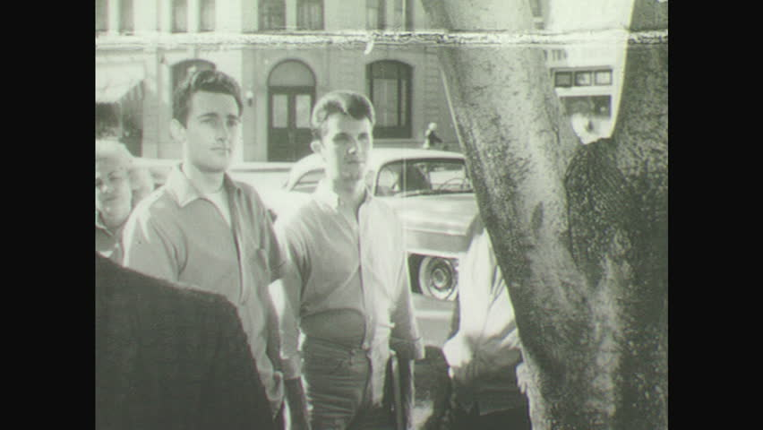 1950s: Man stands by tree in middle of crowd, listens, looks around.   Shutterstock HD Video #29049214