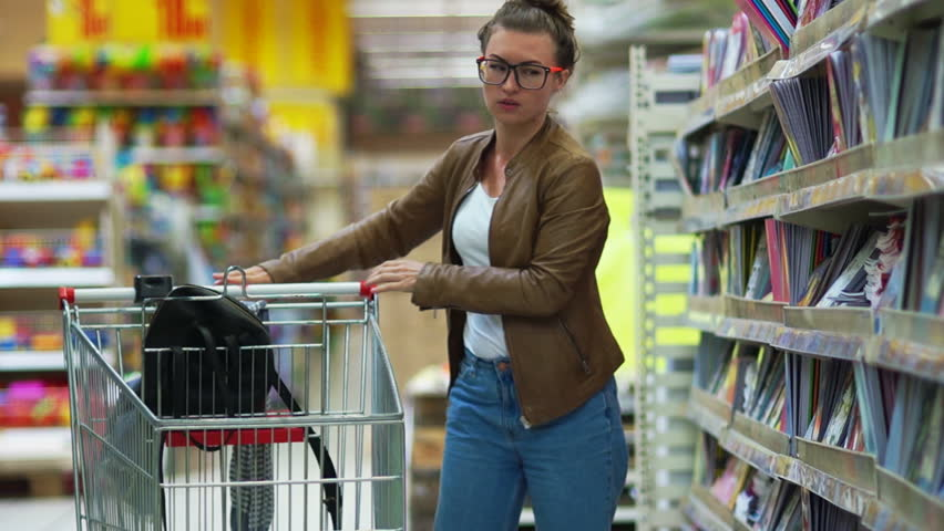 Young beautiful woman buying stationery for school, beautiful mother choose tools in a supermarket for her children, student shopping in a supermarket