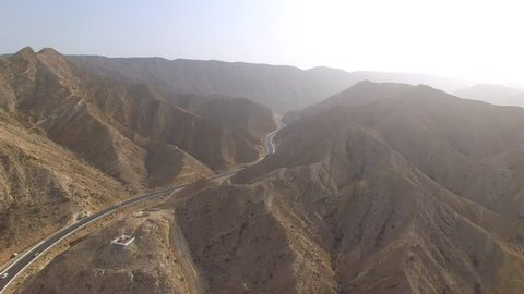 Aerial view of desert valley in Muscat bay region, road in desert surrounded by mountains, Oman, sultanate on Arabian Peninsula from above, 4k UHD