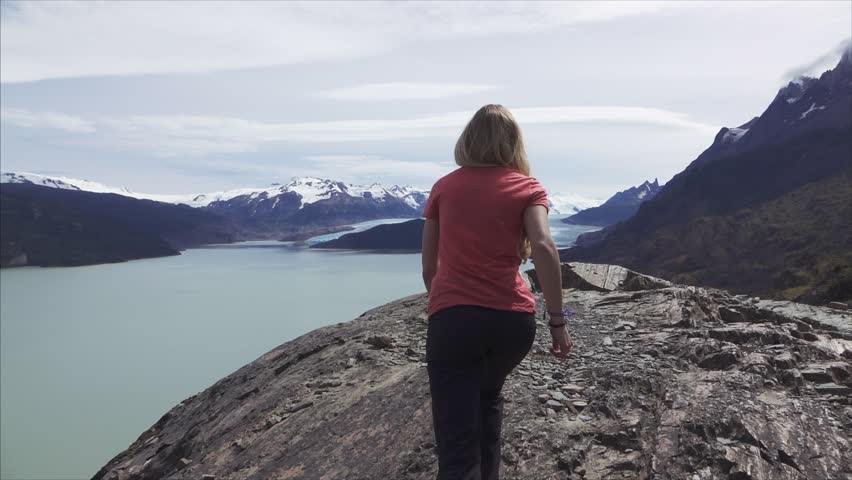 Slowmotion shot of Woman running in Patagonia mountains with glacier Grey