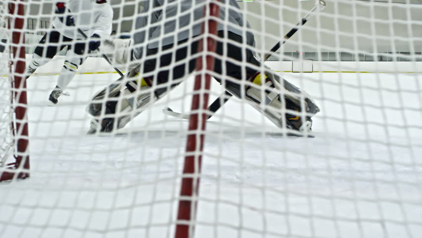 Slow motion shot behind net of hockey goaltender guarding net, then performing butterfly technique to save goal but failing and missing puck shot by forward in white uniform