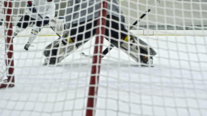 Slow Motion Shot Behind Net Of Hockey Goaltender Guarding Net Then