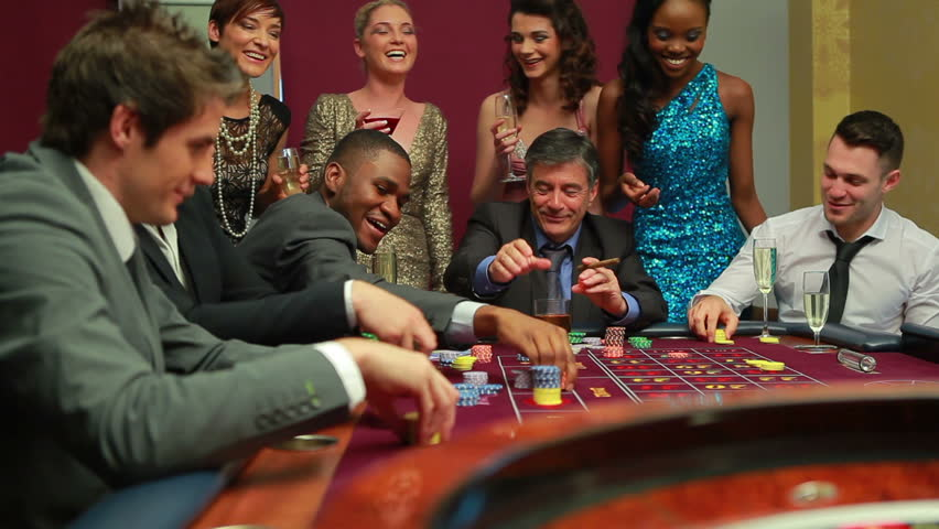 Men placing bets at roulette table watched by women in casino