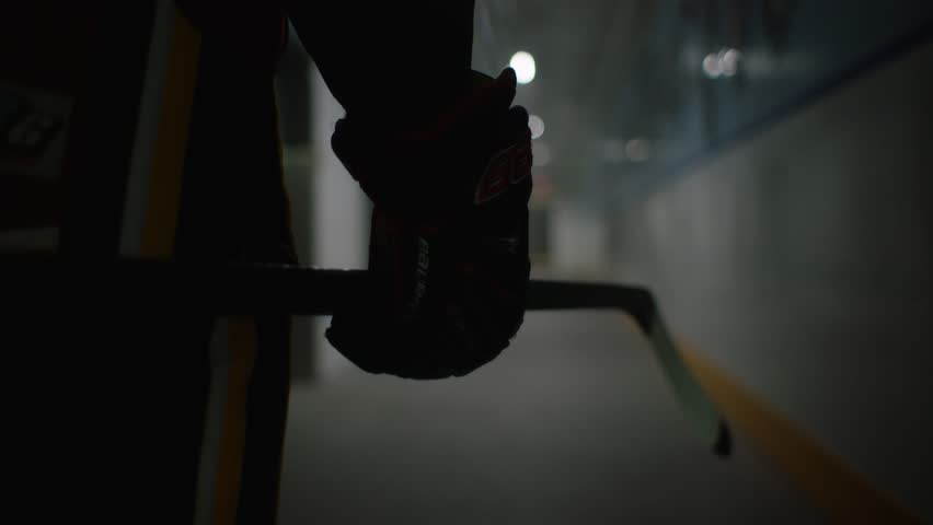 dramatic silhouette of hockey player walking from dressing room into arena twirling their stick glove in slow motion