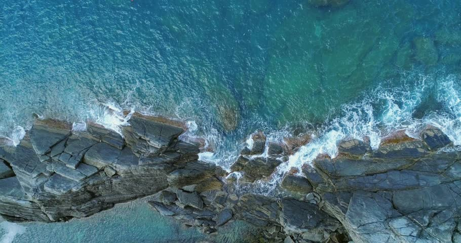 aerial overhead view of ocean mediterranean sea waves reaching and crashing on rocky shore beach coast. Sunny weather. 4k slow motion 60p top view drone video shot