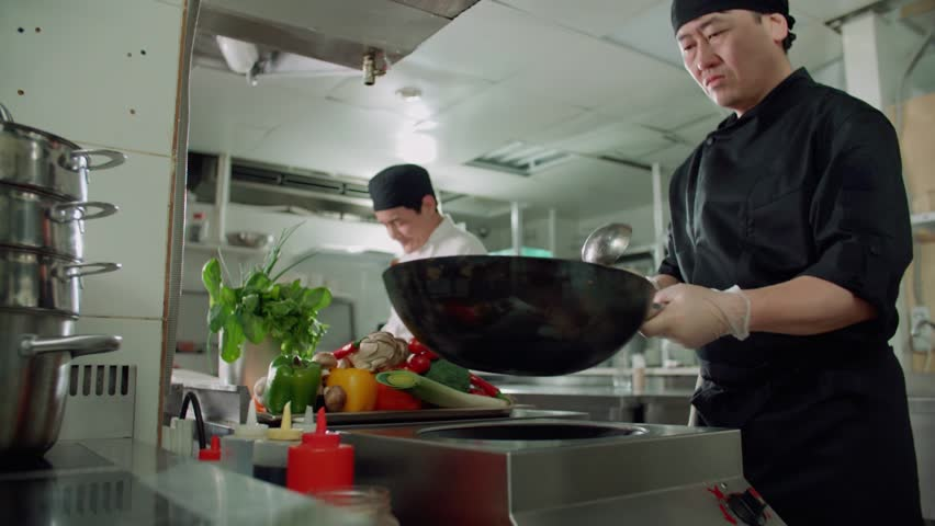 male chef actively working in the kitchen of an Asian restaurant mixed colorful vegetables are roasted in a wok in slow motion