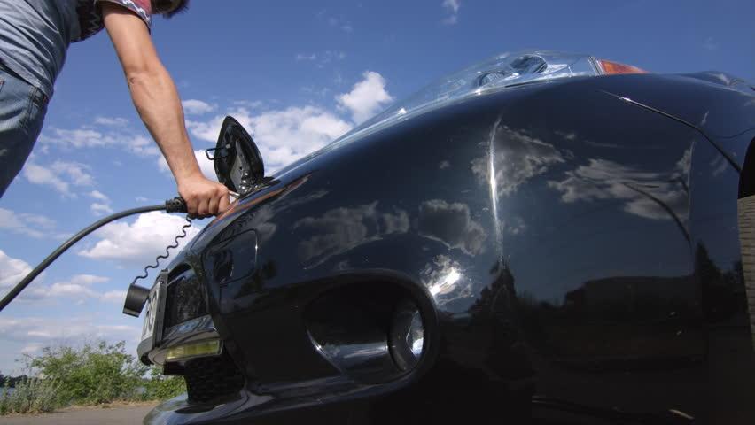 Man plug charging cord into futuristic electric car socket