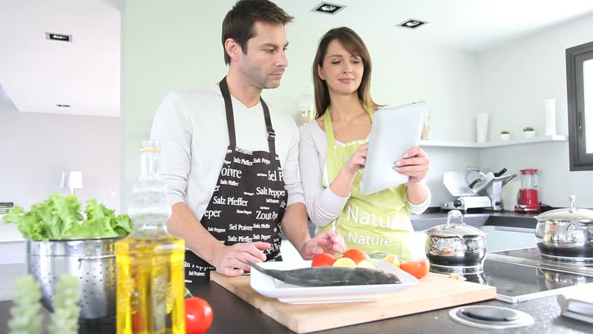 Home Kitchen Cooking couple in home kitchen using electronic tablet stock footage video