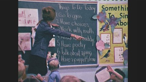 1970s: Teacher stands in classroom at blackboard, points to blackboard. Children raise hands. Children look around, teacher sits next to child, reads books to children. Children play with puppets.