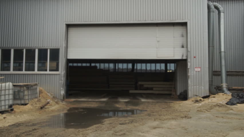 Roller shutter door and concrete floor inside factory building for industrial background. The open door of the hangar