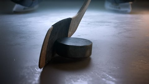 Slow motion hockey stick hitting hockey puck. Close-up