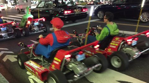 "Tokyo 23 June 2017: Public Road Go Karting Tour ""Real Life Mario Kart"" in Tokyo. Go kart speed ride. Driver in karts wearing colorful dress, racing suit in kart race. Karting show. racers karting.kart"