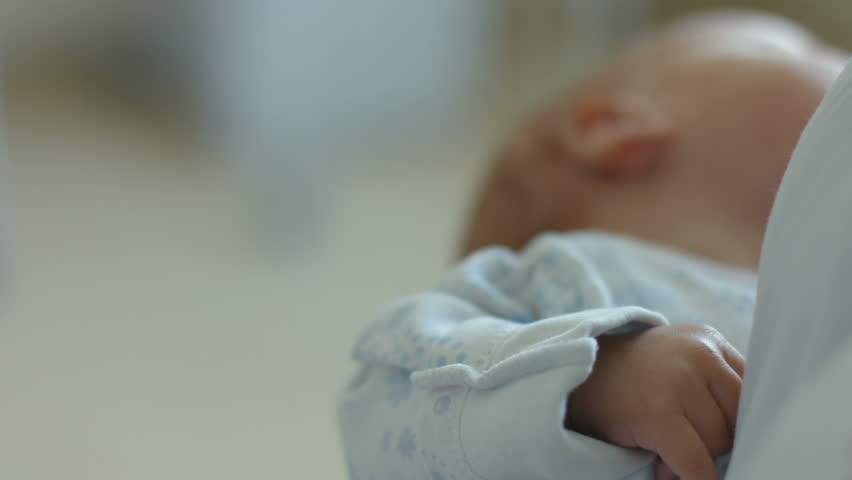 Babys hand in the hand of an adult, care