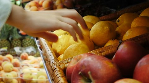 Woman hand choosing lemons at the grocery store picks up lemons at the fruit and vegetable aisle in a supermarket