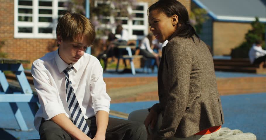4K Kind teacher comes to talk to sad lonely boy outdoors in the school yard. Slow motion